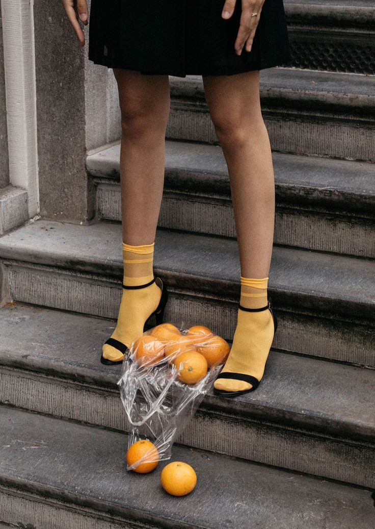 How to wear bright socks with strappy sandals Creative content direction by fashion influencer Beatrice Gutu shoe editorial with oranges in plastic bag aesthetic conceptual photography