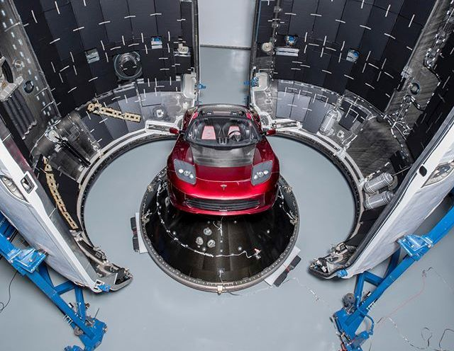 SpaceX CEO Elon Musk is showing off his midnight cherry-red Tesla Roadster sports car being prepared for its ride atop a Falcon Heavy rocket.