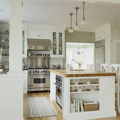 Airy white kitchen with glass front cabinets, butcher block island, open floor plan, upper shelving, spice storage, oven in island. päädyssä oleva hylly