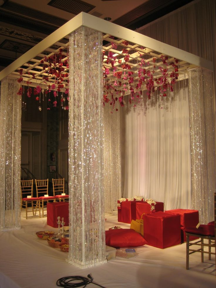 I love this simple but elegant mandap! Although the red boxy seats will have to go to be replace with ivory/gold chairs. :)