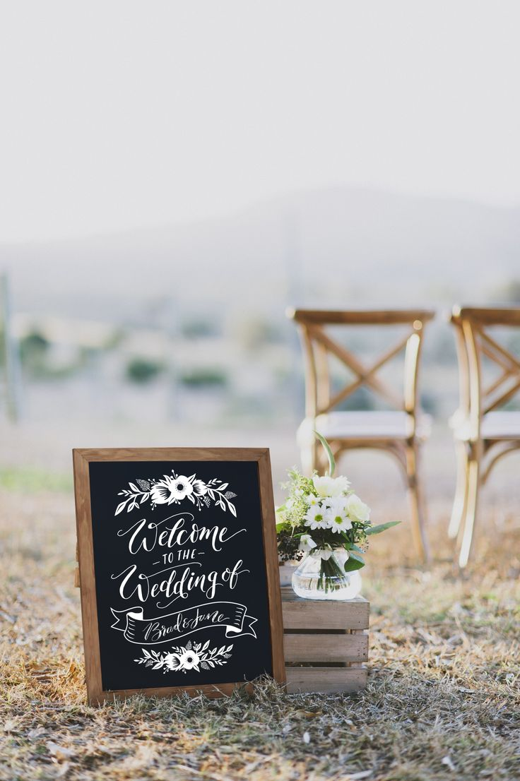 This beautiful wedding welcome chalkboard sign will add the perfect rustic touch to your ceremony. Fill in the bride and groom's name using any standard chalk.  These chalkboards feature printed artwork and is hand-lettered and hand-made in Brisbane, Australia by Fox & Fallow. The chalkboard is 16 x 20″ with a timber and walnut frame.