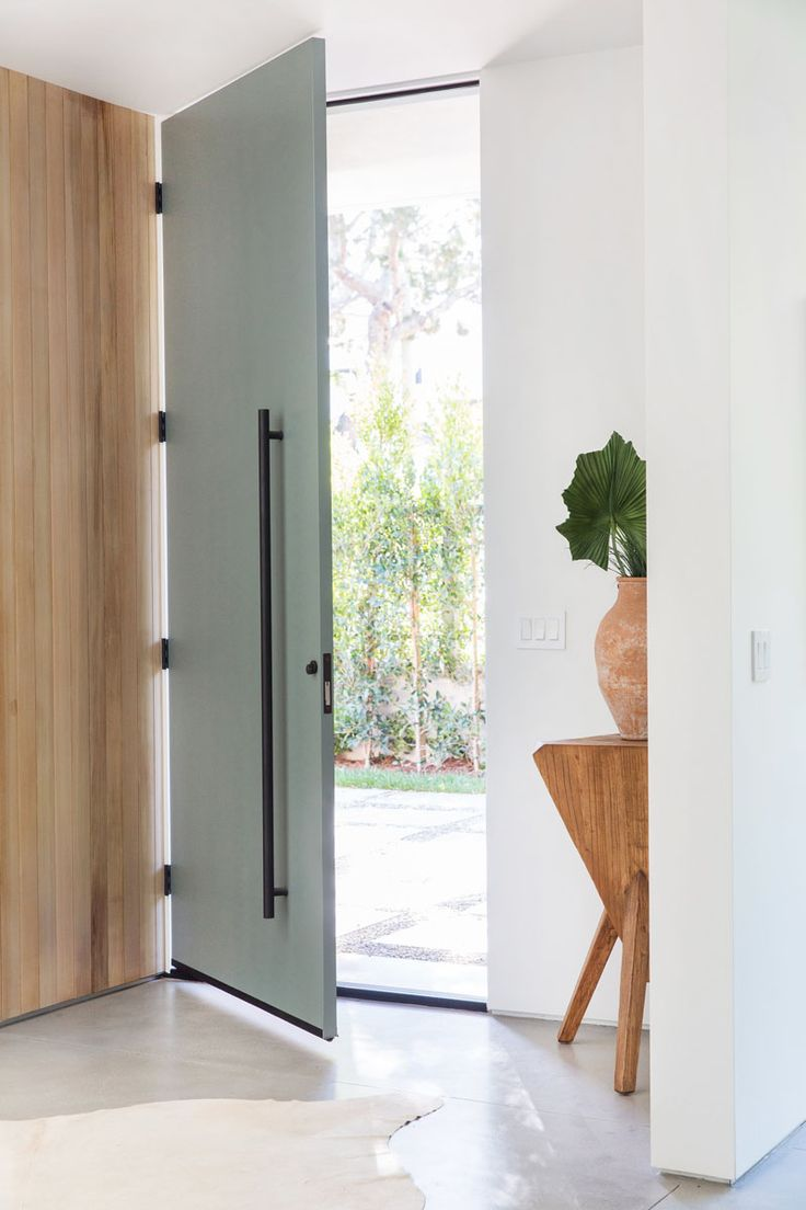 A tall, full-height grey front door with matte black hardware welcomes visitors to this mid-century inspired home. #FrontDoor