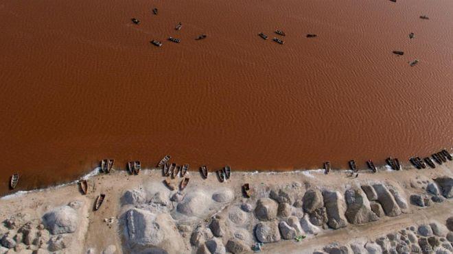 Hồ Retba, Senegal. Trông giống như một hồ bơi khổng lồ chứa đầy nước ngọt màu dâu tây, hồ Retba có độ mặn rất cao, khiến con người có thể dễ dàng nổi trên mặt nước. Đây cũng là nơi nhiều diêm dân tới lấy muối. Hồ nằm gần vùng bờ biển Đại Tây Dương của Senegal. Sắc hồng rực rỡ của nước hồ được tạo thành từ một loại vi tảo ưa mặn có tên là Dunaliella salina, vốn tạo ra sắc đỏ nhằm hấp thụ nắng mặt trời. Màu sắc ở hồ đặc biệt sặc sỡ trong mùa khô.