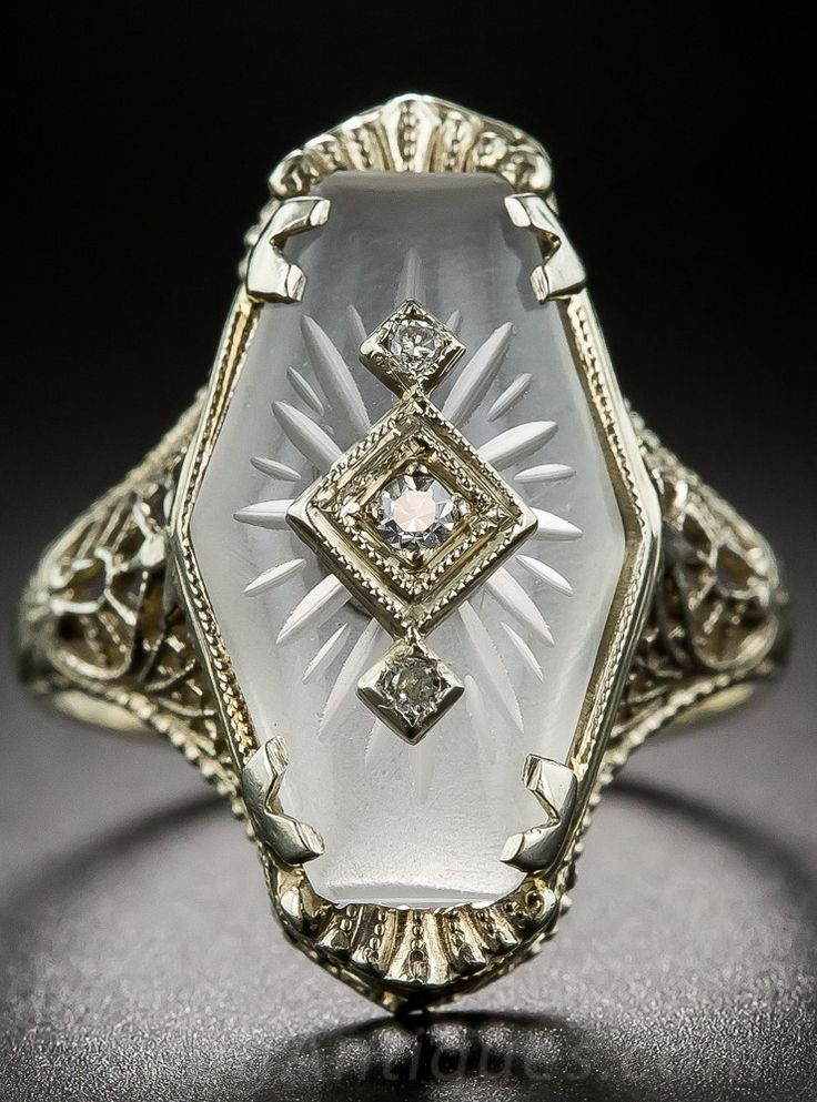 Art Deco Carved Quartz Crystal and Diamond Ring.  A tiny trio of round diamonds twinkle from atop a shimmering, fancy shaped carved quartz crystal (sometimes referred to as camphor glass) in this sweet and lovely depression-era dinner ring, die-struck and hand finished in fabulous filigree with an embossed ring shank.