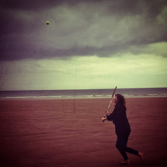 Playing stick-ball on the beach with my lovely lady. I took this photo with an iPhone in the rain.