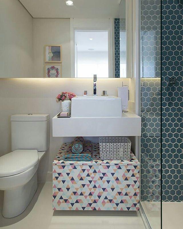 Pequeno banheiro clean e com mix de estampas geométricas. Abaixo da pia, um pequeno baú substitui o armário. Na parte do banho, o material na parede com estampa de hexágonos ficou bem bonito e moderno, o que pode ser uma ótima alternativa para quem não quer usar as famosas pastilhas quadradas