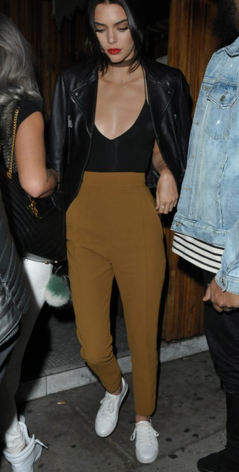 Kendall Jenner wearsa leather Balenciaga biker jacket, blavk camisole, mustard high waisted trousers, a choker necklace, and white Kenneth Cole sneakers on Jan. 18, 2016 in Los Angeles, CA.
