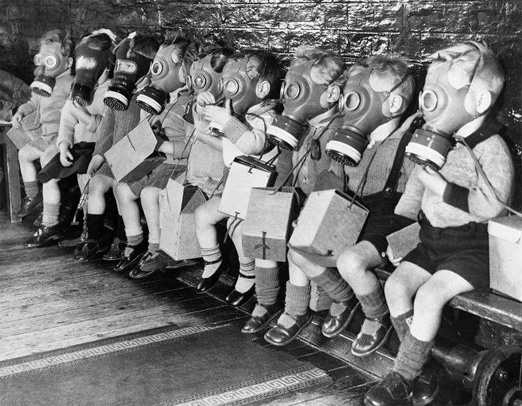 Niños en la escuela, vistiendo máscaras de gas.