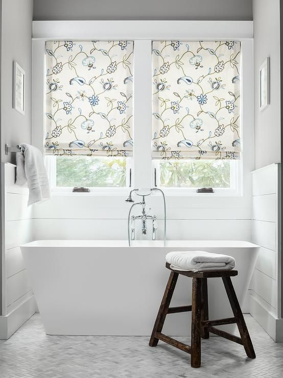 Relax after a long day in a freestanding bathtub paired witha vintage style tub filler fixed in front of white shiplap trim framing windows dressed in brown and blue floral roman shades.