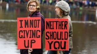 Two women in Seattle hold signs protesting a Trump presidency.