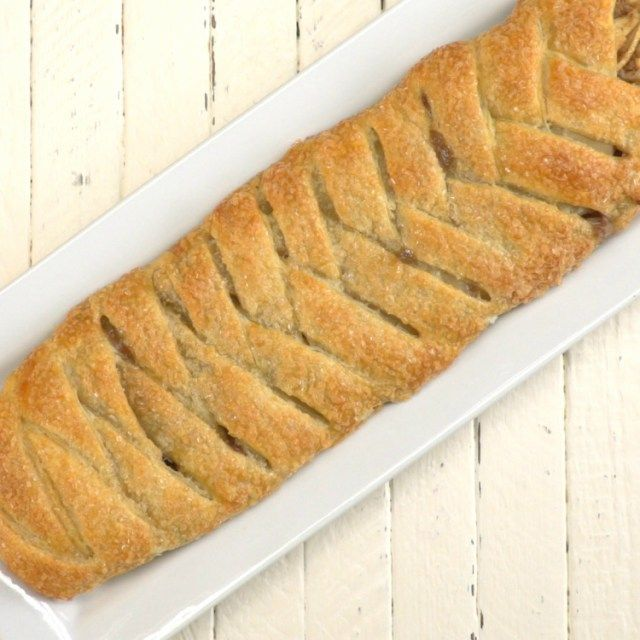 Braided apple walnut strudel on a white plate on a wooden surface