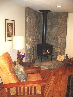 Corner woodstove, black, on raised stone hearth with floor-to-ceiling stone surrounding it. Hardwood floors, white walls.