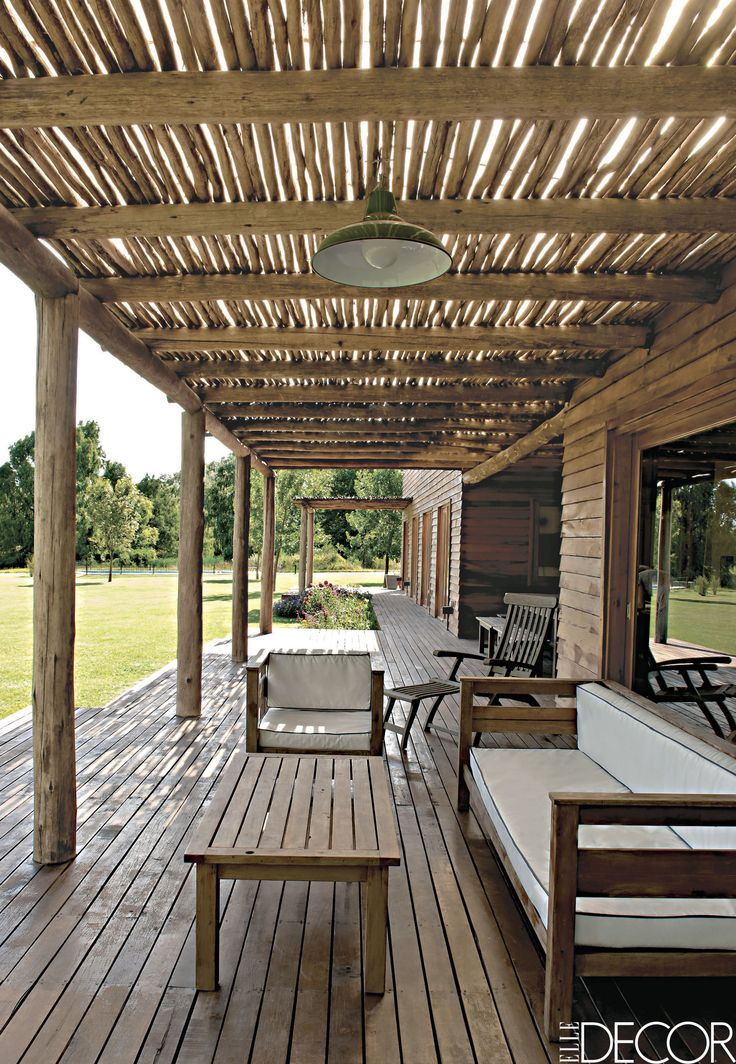 The Buenos Aires-based architecture firm Mazzinghi-Sanchez designed a weekend home in Argentina with a large covered porch and simple wood furnishings. A rustic awning of eucalyptus logs shelters the Brazilian lapacho-wood floor.