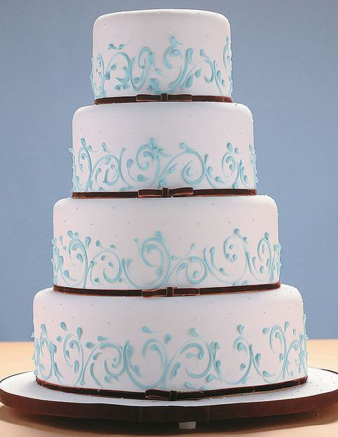 Four tier round white wedding cake with thin brown bands at base and light blue touches.JPG