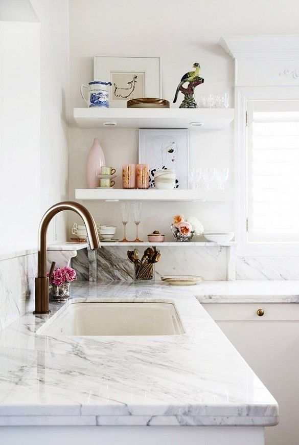 White kitchen with styled open shelves and white marble counter.