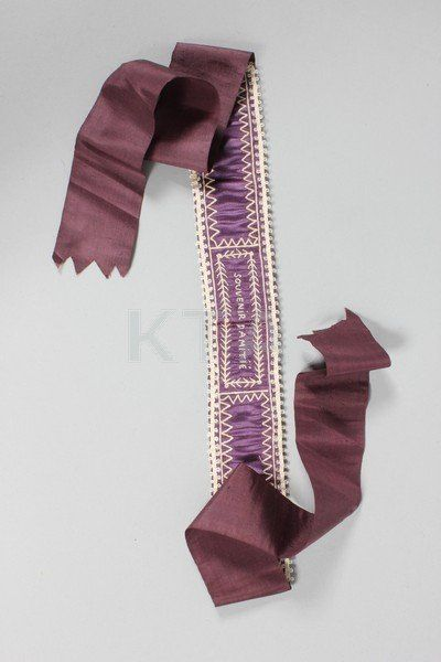 Embroidered silk garter, French, late 18th century. Purple satin embroidered in white chain stitch 'Souvenir d'Amite'.