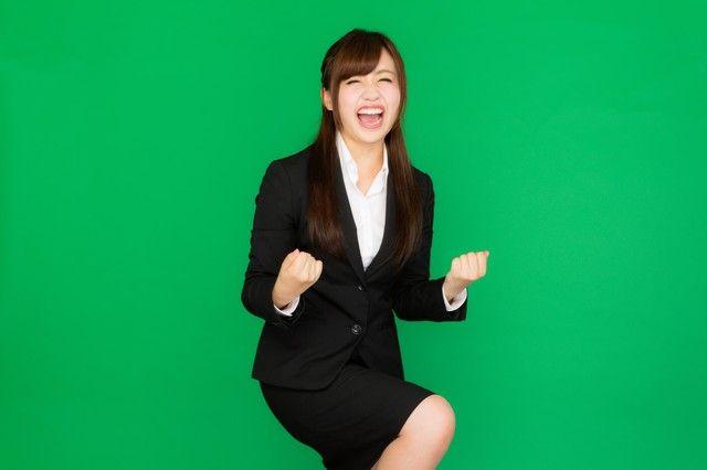 社内プレゼンが通って超喜ぶスーツ姿の女性(グリーンバック)