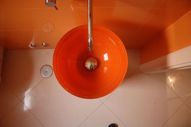 bagno ospiti, dettaglio del lavabo a ciotola in cristallo arancione installato su un pilastrino da noi creato e rivestito in mosaico arancione, rubinetto a parete, pavimento gres porcellanato bianco lucido 60x60, rivestimento bicottura arancione