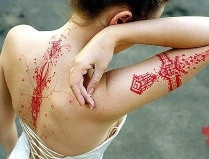 Love all of these intricate, but delicate tattoos. The red ink is fantabulous!