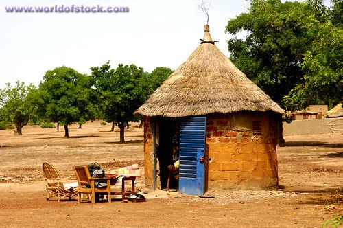 Stock Photo titled: African Round Hut With Thatched Roof And Interior Furniture Placed Outside During Household Clean-up, Burkina Faso, unlicensed use prohibited