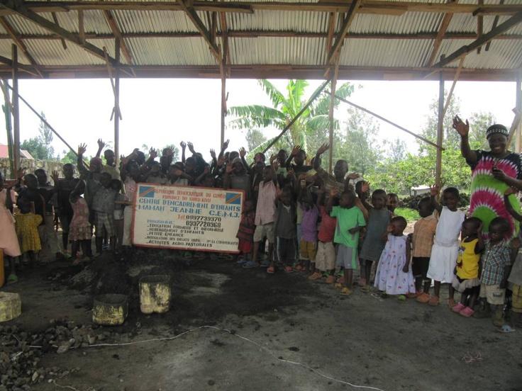 Barn ved Mama Jeanne sitt barnehjem. De står under det nyoppførte taket til kjøkkenhuset. Det gamle huset ble truffet av en granat før jul.