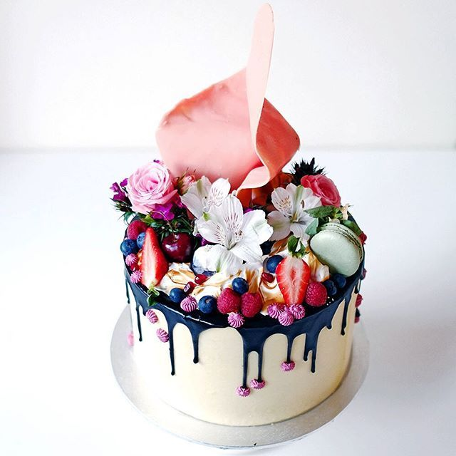 A vanilla layered buttercake with Swiss meringue buttercream topped with mixed berries, macarons, fresh flowers, a huge pink sail, toasted meringue and #burgundy coloured pipings