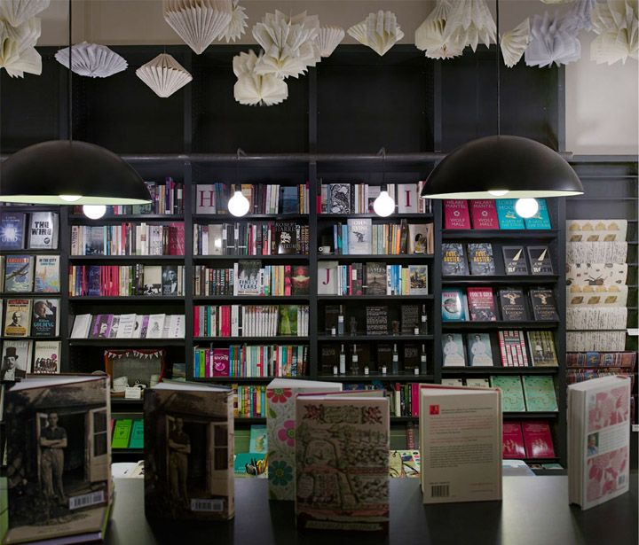 Lutyens Rubenstein London Bookshop In Notting Hill Book Sculptures Hanging From Ceiling Black Shelves Modern Globe Pendants