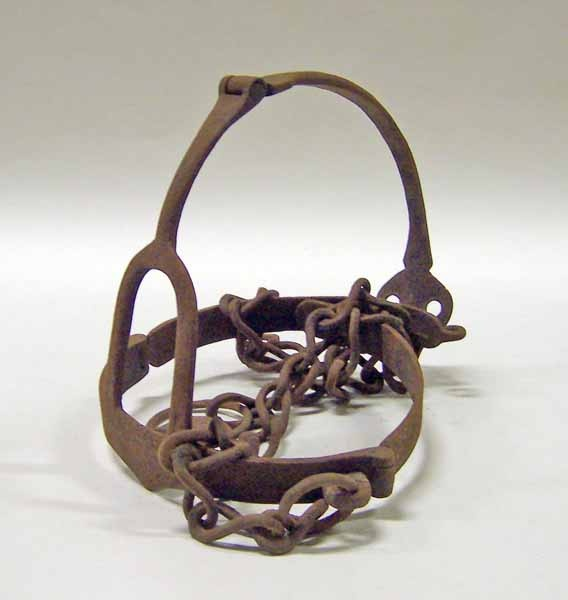 17th century English Scold's bridle at the Manchester Art Gallery, Manchester - In 17th century marriages, the image of the husband in control of the submissive wife was key.  So a woman who was known to henpeck or scold her husband could be made to wear the scold's bridle as a form of public humiliation.  The device consisted of a metal structure that was fitted over the head, with a metal plate that went into the woman's mouth, clamping down her tongue and preventing her from speaking.