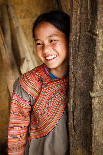 Vietnam | Portrait of a Flower H'mong hill tribe girl wearing traditionally colourful clothing, in a small village between Coc Ly and Cao Son. Lao Cai |  | © Kimberley Coole