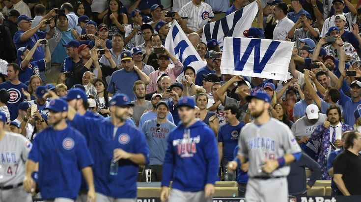 Chicago Cubs fans hold up victory flags after the Cubs defeated the host Los Angeles Dodgers 8-4 in Game 5 at Dodger Stadium. The series, which the Cubs lead three games to two, resumes Saturday at Chicago's historic Wrigley Field.