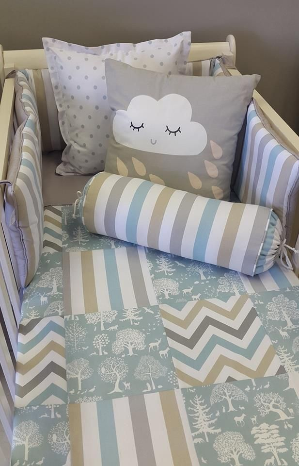 Padded cot bumper in Stripes, Duck Egg, Taupe and Grey. Scatter cushion with cloud face and rain drops. Bolster cushion in our Stripes, Duck Egg, Taupe and Grey. Patchwork cot duvet cover in our Little Woodlands, Duck Egg, Stripes, Duck Egg, Taupe and Grey, and Zig Zags, Duck Egg, Taupe and Grey. Scatter cushion in Spots, White and grey.