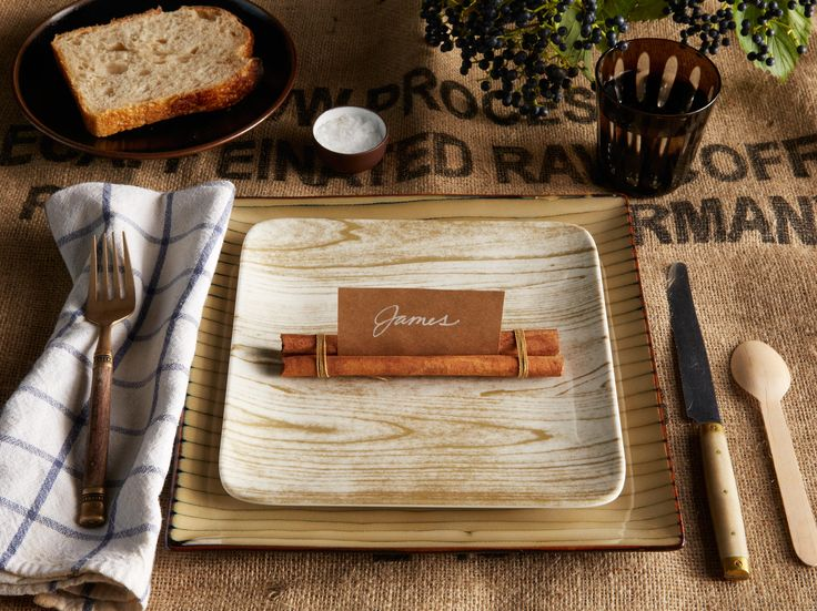 Woodgrain plates are an ideal item for a rustic tablescape, now decorate each one with cinnamon sticks that have been tied together to create homemade placecards.
