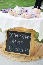 Blind folded diaper changing.  white board with score sheet and prize for winner