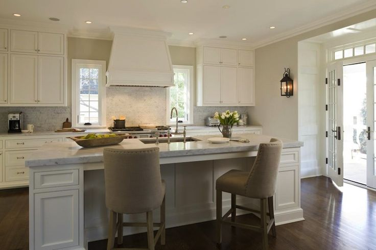 Elegant, light filled kitchen with custom cabinetry and central island with bar seating. French doors with transom window. Carriage house style sconces, marble countertops and backsplash. .