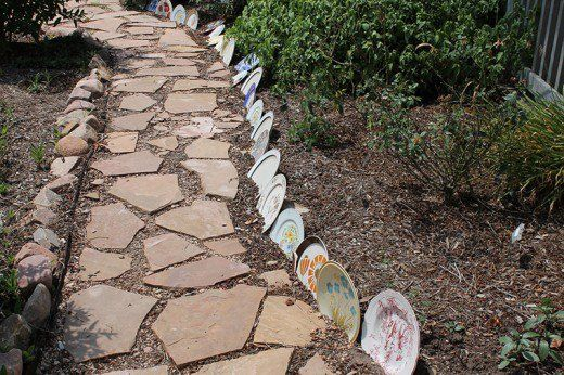 Save the landfills and green up your garden spaces with interesting art work using colorful glass bottles, mismatched dishes, and other items destined to be trashed.