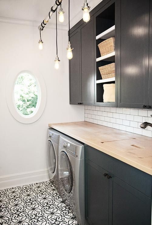 Gillian Pinchin Black And White Laundry Room Features Bulb Pendants Hung From A Tension Rod Over Cement Floor Tiles In