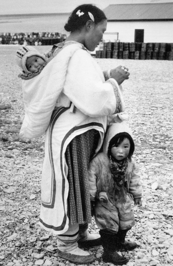Inuit mother with one child in front of her and carrying one in her hood, September 12, 1958. [Igloolik (iglulik), Nunavut] Source: Library and Archives Canada, Charles Gimpel fonds