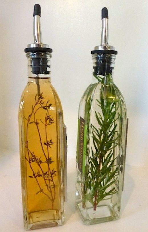 Thyme flavored apple cider vinegar is garnished with a fresh sprig of thyme.  Rosemary and white wine vinegar is decorated with fresh rosemary.