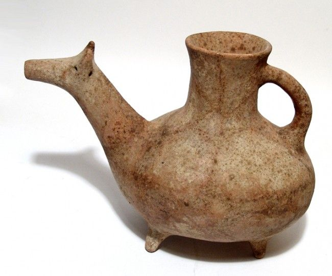 Parthian pottery vessel in the form of bull, Northern Iran, 3rd-1st century B.C. The body globular with four peg feet, and a single handle attaching to a flared mouth, the spout is in the form of a stylized bull head, the horns curved inward and the eyes indicated by small holes, 21.6 cm high. Private collection