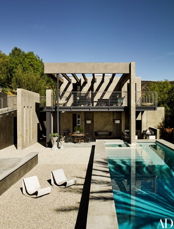 The pool terrace at Ryan Murphy's California compound, designed by architect Mark Singer, features chairs and planters by Willy Guhl   archdigest.com