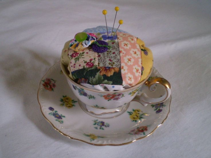 Scrappy log cabin quilt block made into pincushion using vintage teacup.