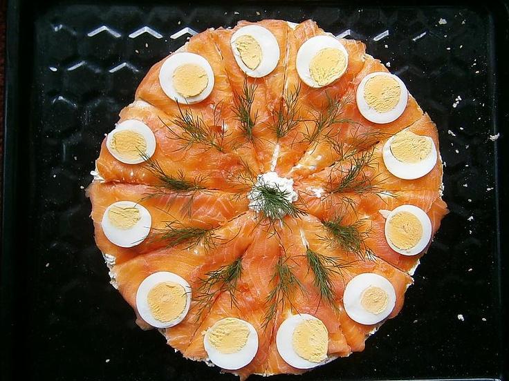 Fladen-Tortenboden mit Frischkäse und Kräuterquark, je nachdem, was man gerne mag dick bestreichen. Wäre sozusagen dann die Creme-Tortenfüllung. Dann den Lachs in mund- und bissgerechte Häppchen schneiden (oder einfach reißen) und die Torte damit belegen. Zum Schluss auf jedes Tortenstück eine Scheibe Ei und mit frischem Dill garnieren.