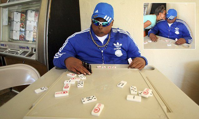 Dead gangster's body is propped up playing a game of DOMINOS