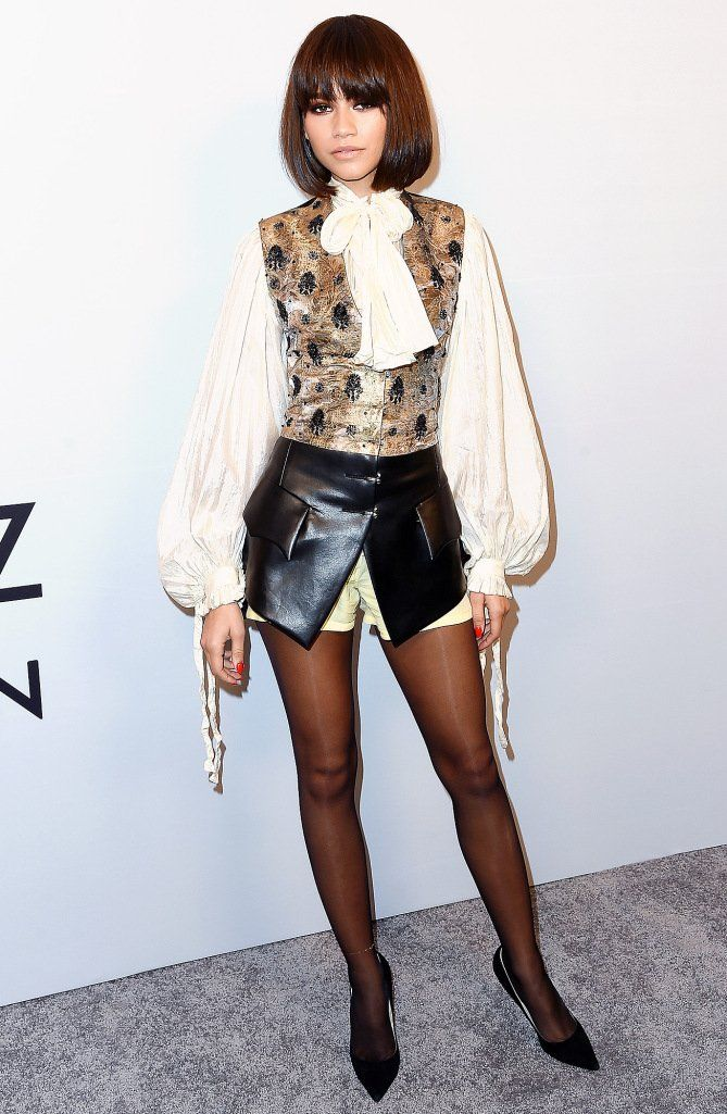 Zendaya in a bow blouse, leather mini and tights