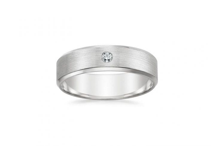 ''Fiero'' Wedding Band Round Cut Diamond An attractive band with contemporary detail, this distinctive ring features a sparkling diamond that is flush set in a soft matte finish and balanced with two polished beveled edges. The interior has a rounded inside edge for increased comfort.  Band Width: 7 mm. 1 Diamond 0.10cts total.