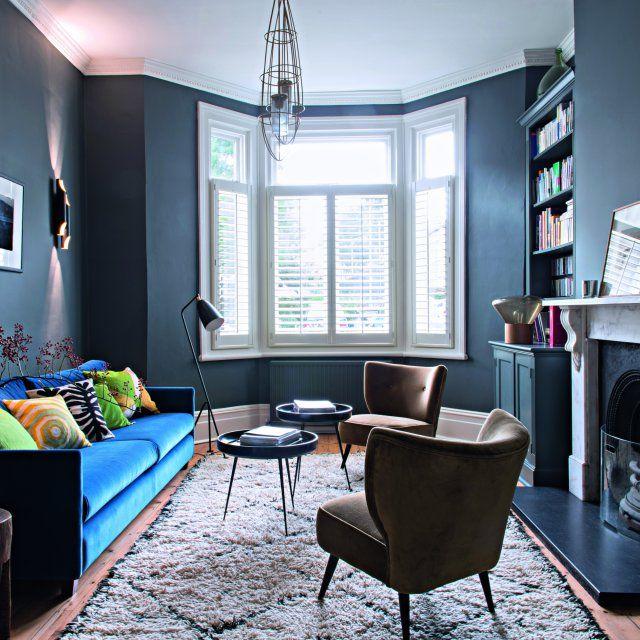"""Dans le salon de cette maison bleue, Aude a opté pour la teinte """"Down Pipe"""" de Farrow&Ball. Canapé sur mesure tapissé de velours Designers Guild. Coussins India Mahdavi. Au sol, tapis Beni Ouarain vintage, Maroc Tribal."""