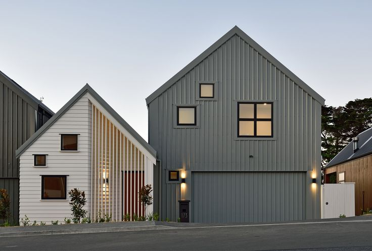 A modern and artistic exterior, this stunning townhouse features a combination of vertical corrugated iron cladding, white horizontal weatherboards, and a timber feature to the entryway (ID 1248)