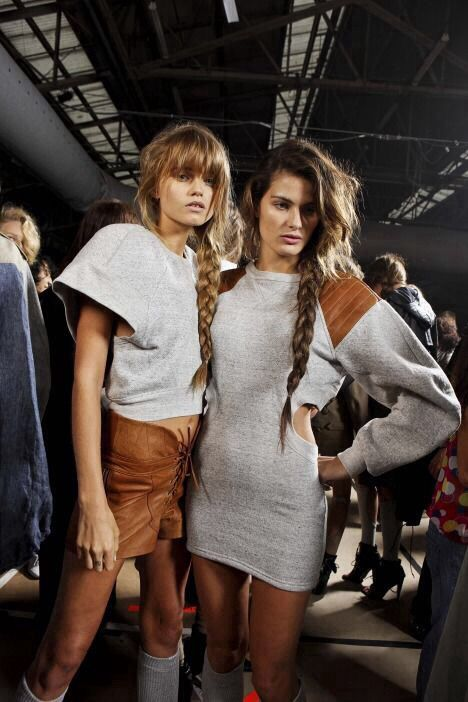 Models backstage in a grey jersey and brown leather combination