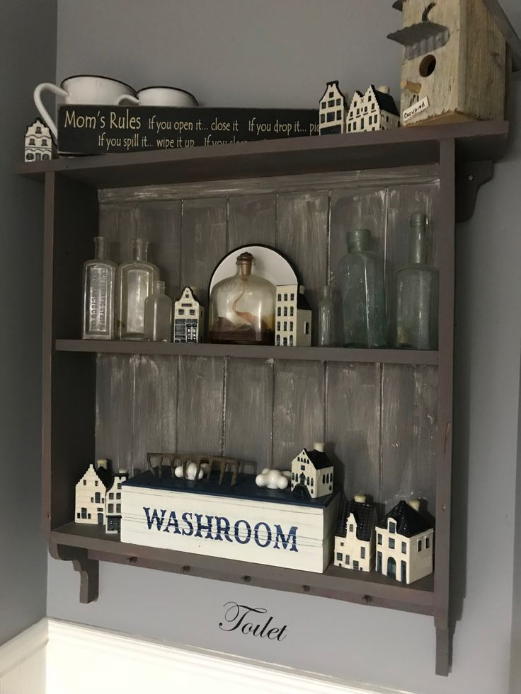 Simple wood shelf with tongue and groove backing displays old medicine bottles and KLM Houses.