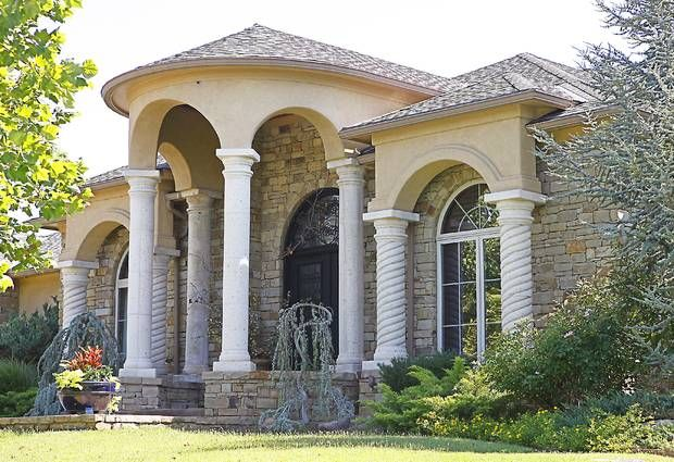 homebuilder perry rice s home features a low pitch roof columns and